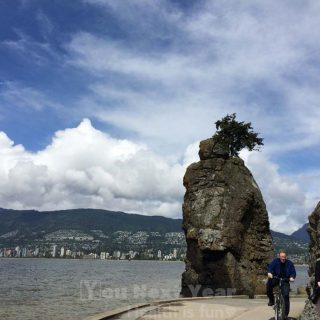 Cyclists round the corner at Siwash Rock on the Stanley Park Seawall. You can see West Vancouver across the water, in the background. Skies are deep blue with distinct white clouds